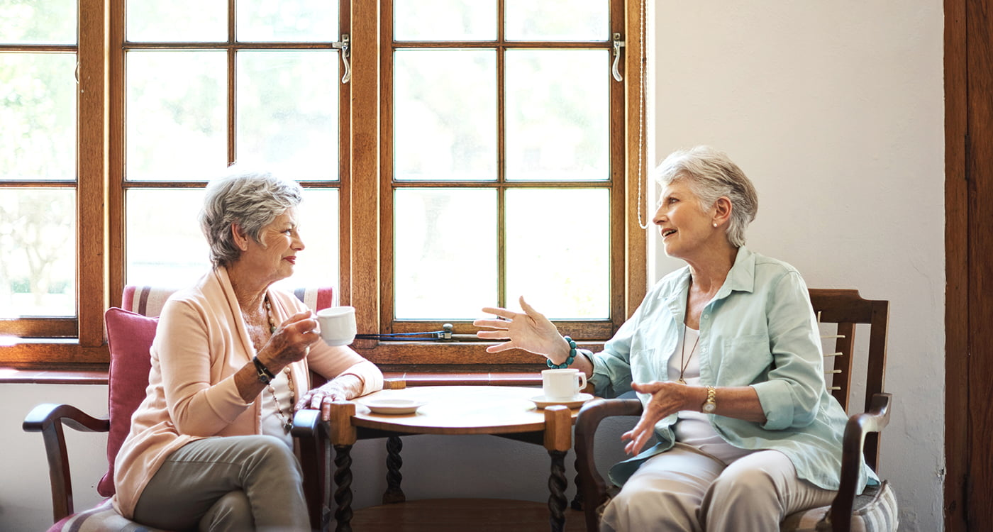 Two older ladies sitting at a coffee table